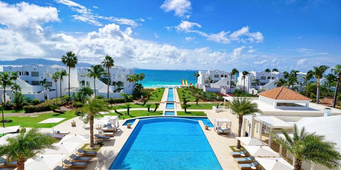 Travel destination showing gorgeous hotel with landscaping including pool and palm trees with beach at end of hotel villas