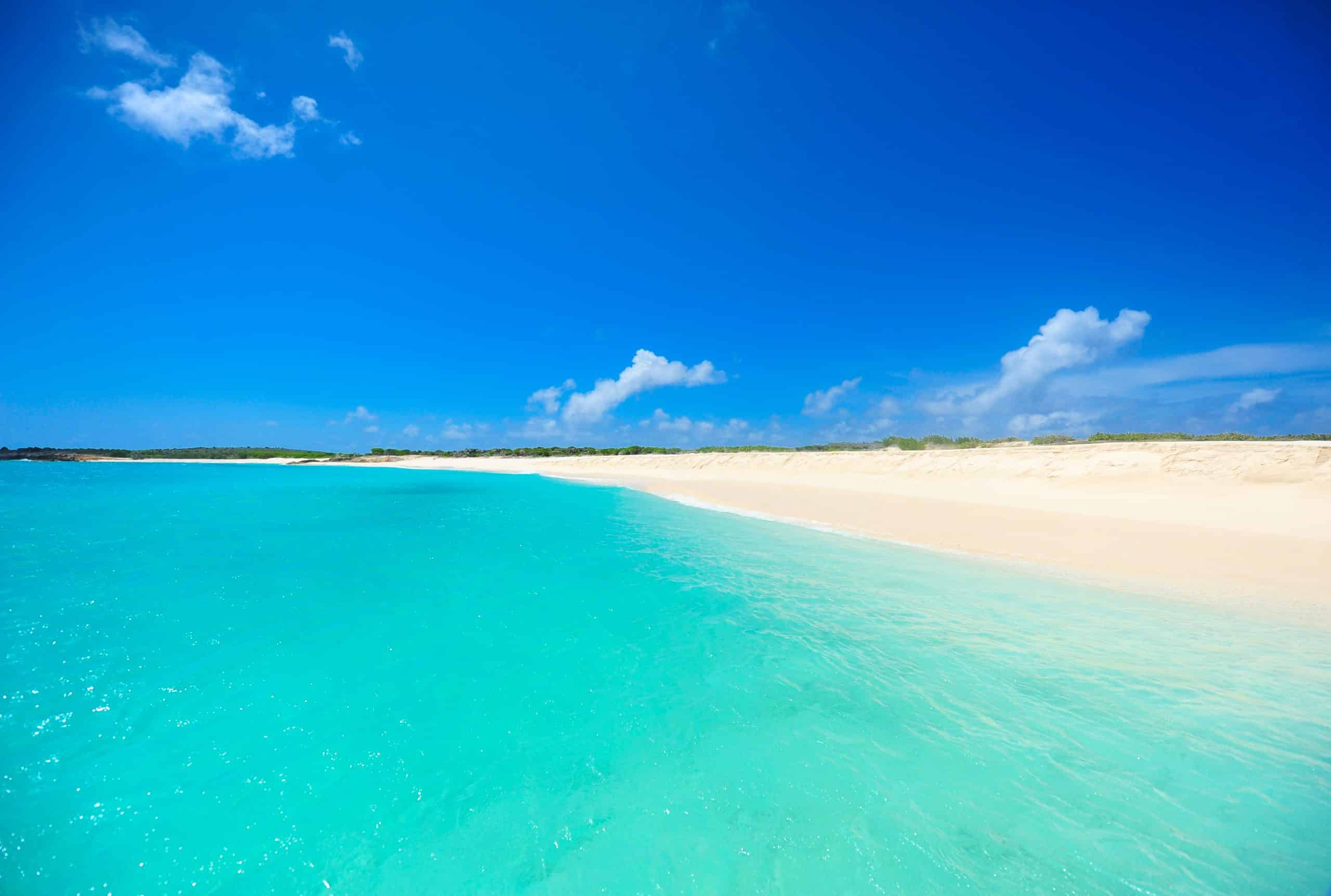 Travel Destination showing beautiful beach with stunning sand and water for miles and almost cloudless sky