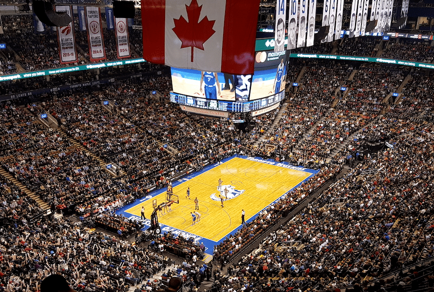 The Air Canada Centre filled with spectators for a Toronto Raptors game with basketball players on the basketball court, the Canadian flag on display and scoreboard
