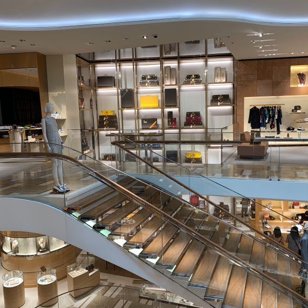 Luxury Retail Department Store showing beautiful large staircase with person on stairs separating 2 levels of retail goods and other people in the store